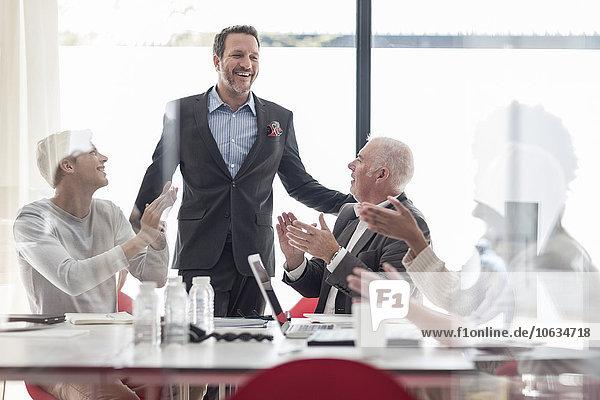 Kollegen applaudieren für Geschäftsmann im Konferenzraum