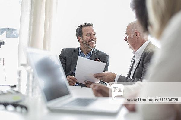 Zuverlässige Geschäftsleute mit Dokumenten und Laptop im Konferenzraum