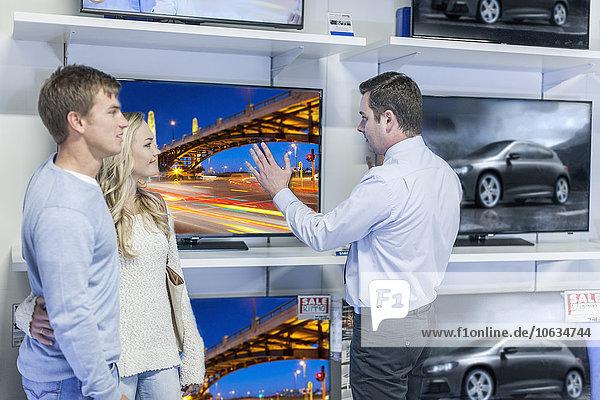 Verkäuferin  die dem jungen Paar Flachbildfernseher zeigt
