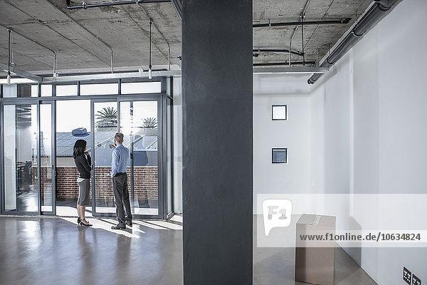 Geschäftsleute im neuen offenen Büro mit Blick aus dem Fenster