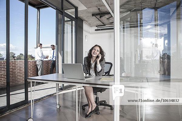 Geschäftsfrau sitzt am Schreibtisch und redet am Telefon