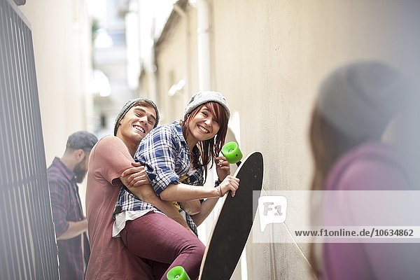 Friends with skateboard having fun in a passageway
