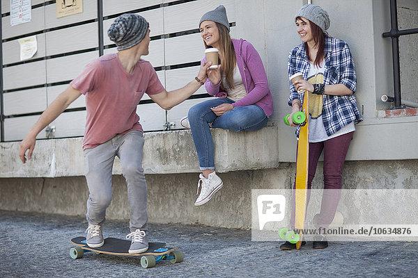 Junger Mann mit Freunden beim Skateboardfahren