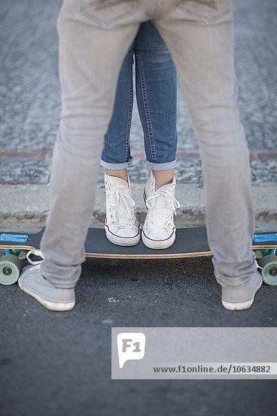 Junges Paar mit Skateboard auf der Straße