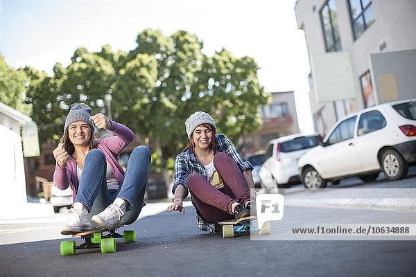 Zwei Freunde sitzen auf Skateboards und fahren die Straße runter.