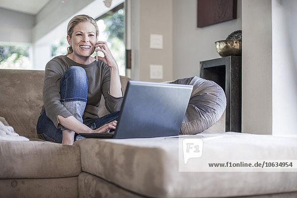Frau sitzt auf der Couch mit Handy und Laptop