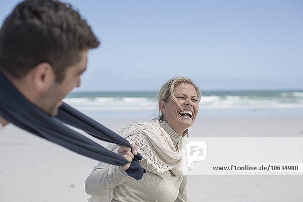 Porträt einer lachenden Frau mit Spaß am Strand