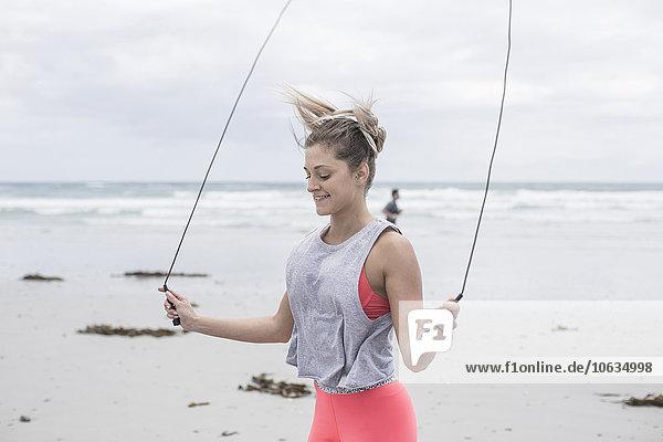 Junge Frau beim Training am Strand mit Springseil