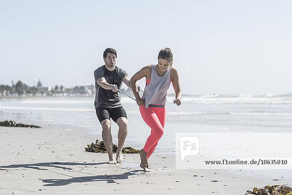 Junger Mann und Frau beim Training am Strand