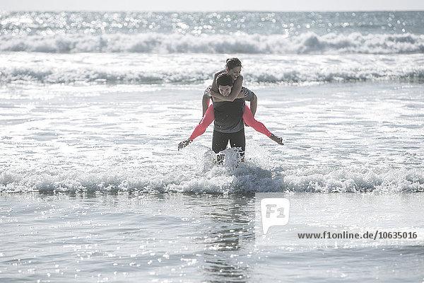 Junger Mann mit Freundin Huckepack im Meer