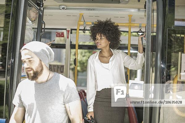 Leute  die aus dem Stadtbus aussteigen.