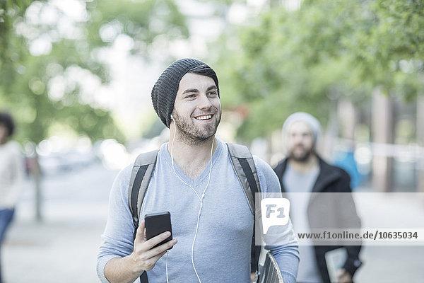 Junger Mann  der in der Stadt spazieren geht und Musik hört.