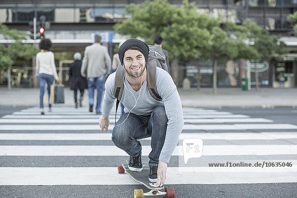 Junger Mann beim Skateboarden auf Zebrastreifen