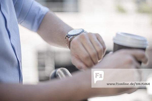 Junger Mann kontrolliert die Zeit  schaut auf die Armbanduhr.