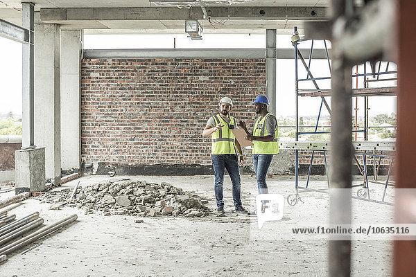 Bauarbeiter diskutieren auf der Baustelle