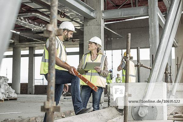 Frau in Schutzkleidung und Bauarbeiter diskutieren auf der Baustelle