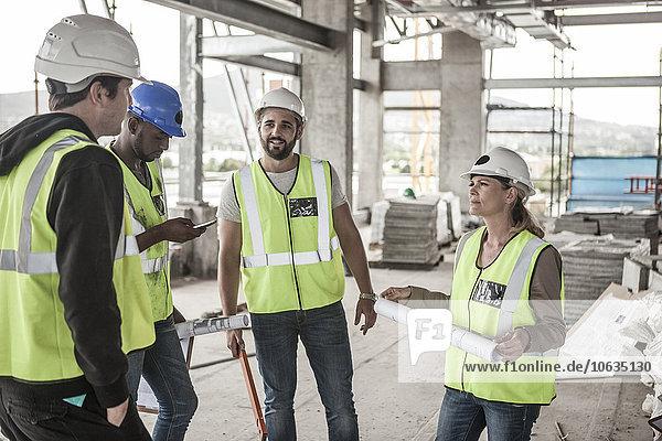 Frau in Arbeitsschutzbekleidung und Bauarbeiter auf der Baustelle