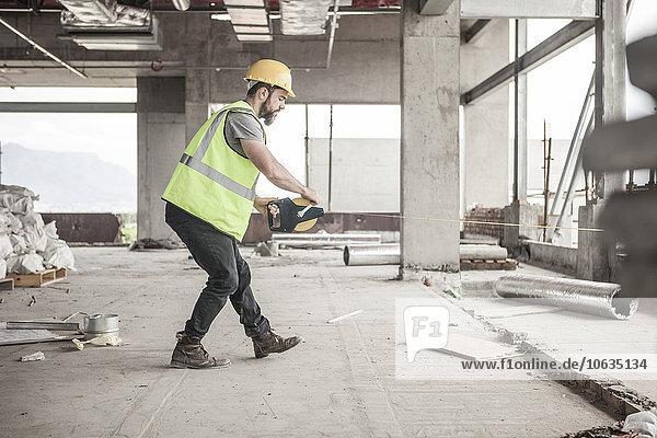 Bauarbeiter mit Maßband auf der Baustelle