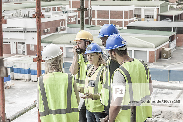 Construction workers and architects talking on construction site
