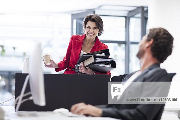 Geschäftsfrau im Büro mit Aktenordner und Blick auf den Kollegen