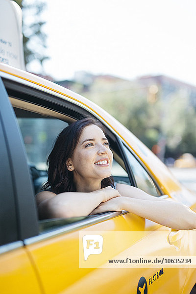USA  New York City  Porträt einer lächelnden jungen Frau  die durch das Fenster eines gelben Taxis schaut.
