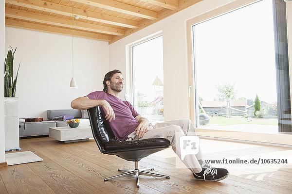 Der reife Mann sitzt entspannt in seinem Wohnzimmer.