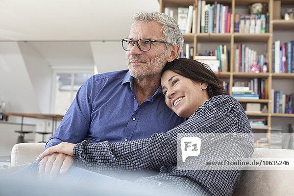 Lächelndes reifes Paar beim Kuscheln zu Hause