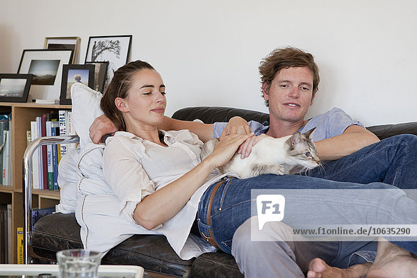 Junges Paar auf dem Sofa liegend mit Katze