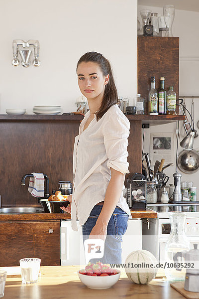 Young woman standing in kitchen  portrait