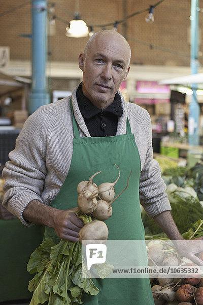 Mature man holding turnip  portrait