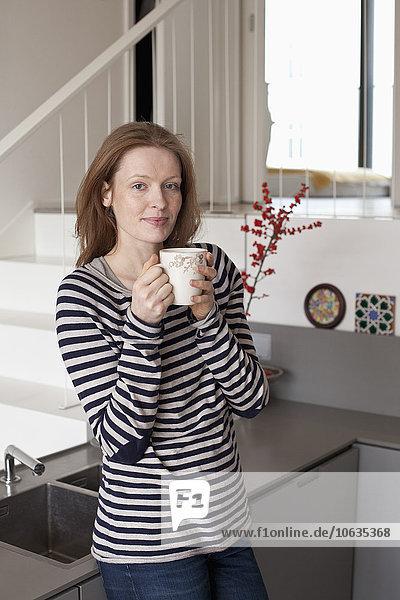 Frau hält Kaffeetasse  Portrait