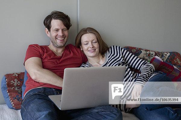Paar mit Laptop auf dem Sofa liegend