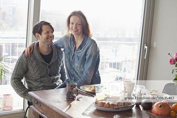 Paar sitzend am Esstisch mit Frühstück