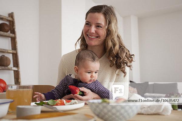 Lächelnde Frau schaut weg  während sie mit einem kleinen Mädchen zu Hause sitzt.