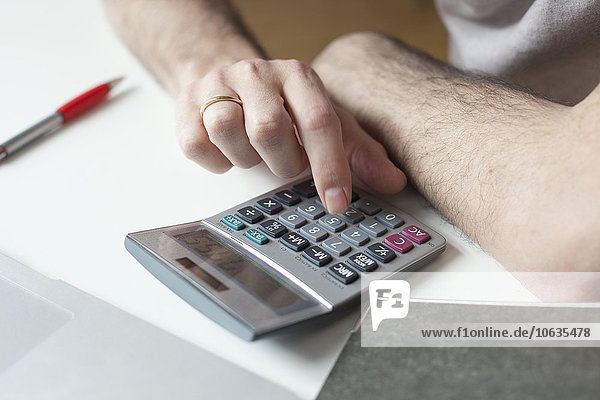 Cropped image of man using calculator at table