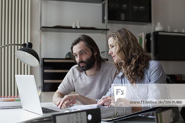 Mittleres erwachsenes Paar  das zu Hause am Laptop arbeitet