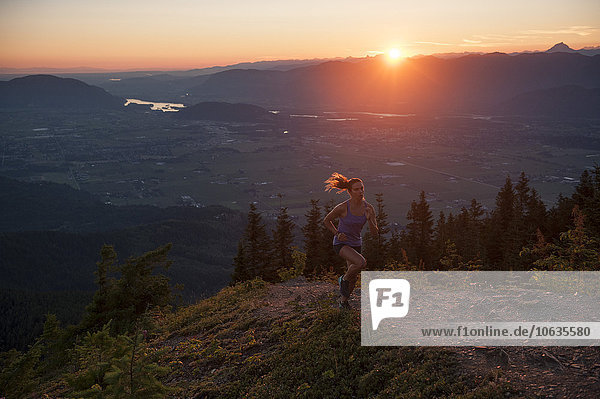 Frau beim Joggen auf dem Bergweg bei Sonnenaufgang Frau beim Joggen auf dem Bergweg bei Sonnenaufgang