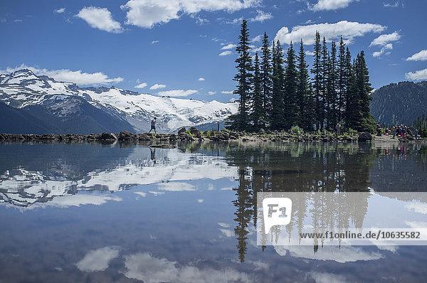 Spiegelungen von Bäumen und schneebedeckten Bergen am Garibaldi-See Spiegelungen von Bäumen und schneebedeckten Bergen am Garibaldi-See