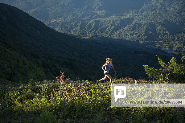 Frau läuft auf Bergpfad Frau läuft auf Bergpfad