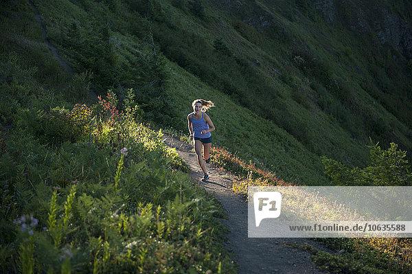 Volle Länge der Frau beim Joggen auf dem Bergweg