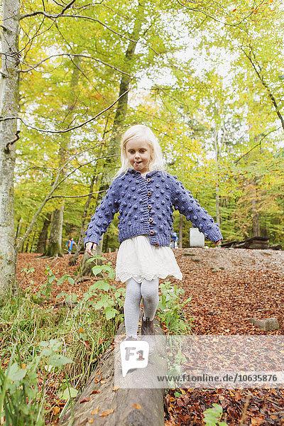 Girl walking on log in park