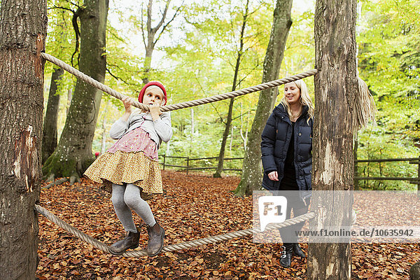 Mother looking at girl balancing on rope in forest