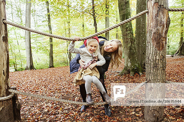Happy mother assisting girl balancing on rope in forest