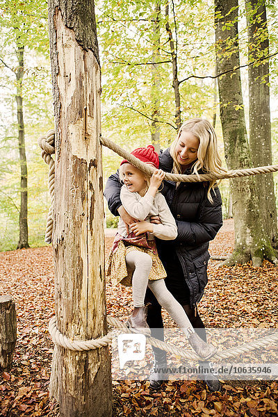 Happy mother assisting daughter balancing on rope in forest