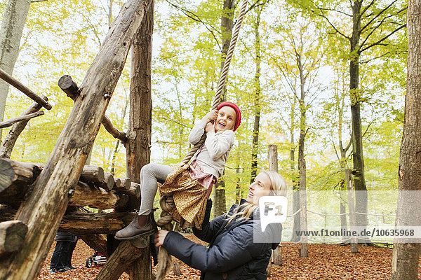 Woman assisting girl balancing on rope swing in forest