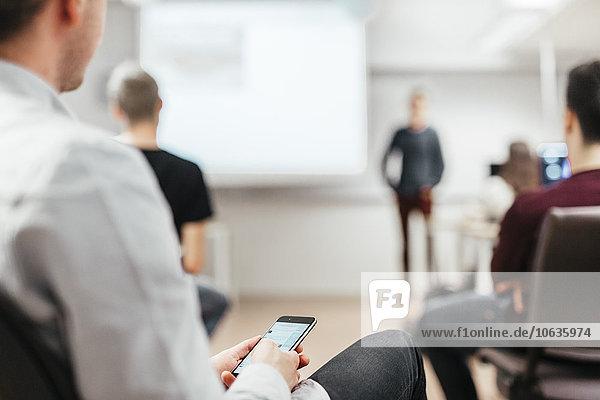 Mittlerer Ausschnitt halten Klassenzimmer Student Smartphone Medien