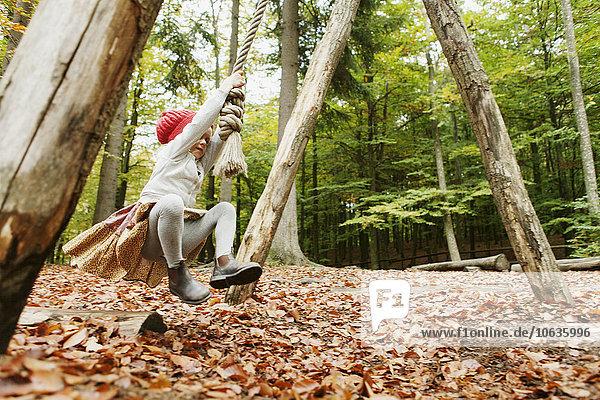 Girl swinging in forest
