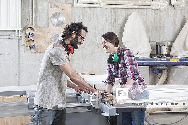 Seitenansicht der lachenden Mitarbeiter mit einer Formatkreissäge in der Werkstatt