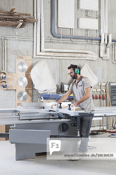 Full length of male carpenter using a sliding table saw in workshop