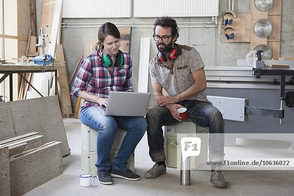 Volle Länge der mittleren erwachsenen Schreiner mit Laptop in der Werkstatt